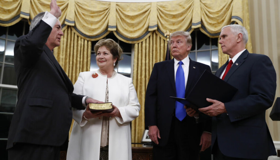 President Donald Trump watches as Vice President Mike Pence swears in Rex Tillerson as Secretary of State in the Oval Office of the White House in Washington, Wednesday, Feb. 1, 2017. Holding the Bible is Tillerson's wife Renda St. Clair. (AP Photo/Carolyn Kaster)