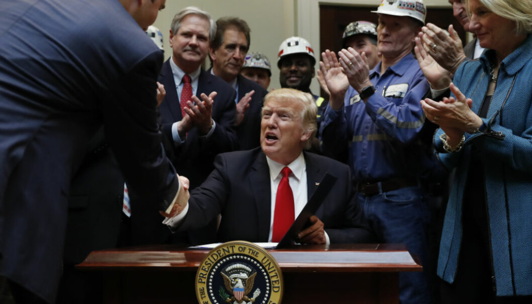 President Donald Trump, joined by coal miners and members of Congress including Sen. Shelley Moore Capito, R-W.Va., right, and Sen. Joe Manchin, D-W.Va., second from right, is congratulated after signing H.J. Res. 38 in the Roosevelt Room of the White House in Washington, Thursday, Feb. 16, 2017. (AP Photo/Carolyn Kaster)