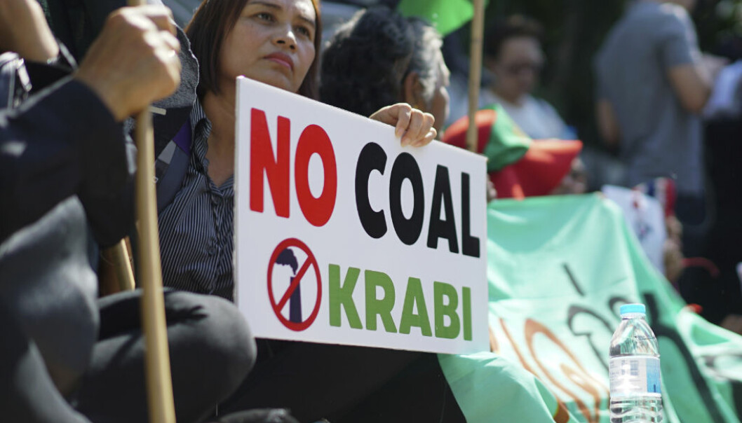 A woman holds up a sign against a proposed coal-fired plant on Thailand's coast, in Bangkok, Thailand, Feb. 17, 2017. Thai government's committee approved construction of an 800-megawatt coal power plant near pristine beaches on the Andaman Sea, Prime Minister Prayuth Chan-ocha announced Friday. The plant and an accompanying dock are slated to be built next to an existing oil plant on the coast in Krabi, a major tourist destination. (AP Photo/Dake Kang)