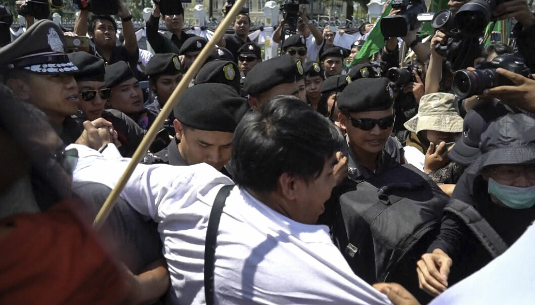 In this image made from video, Tadpong Kadam, a Bangkok student, struggles against police during a demonstration against a proposed coal-fired plant on Thailand's coast, in Bangkok, Thailand, Feb. 17, 2017. Thai government's committee approved construction of an 800-megawatt coal power plant near pristine beaches on the Andaman Sea, Prime Minister Prayuth Chan-ocha announced Friday. The plant and an accompanying dock are slated to be built next to an existing oil plant on the coast in Krabi, a major tourist destination. (AP Photo)