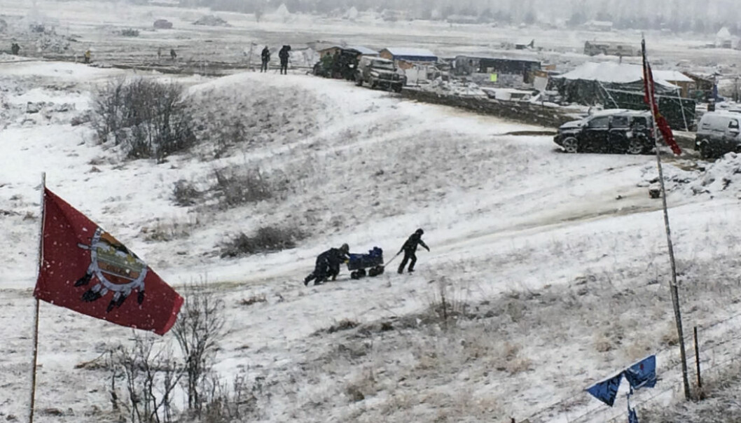 People push belongings up a hill at the Dakota Access pipeline opponents' main protest camp in southern North Dakota near Cannon Ball, N.D., on Wednesday, Feb. 22, 2017, as authorities prepared to shut down the camp in advance of spring flooding season. (AP Photo/Blake Nicholson)