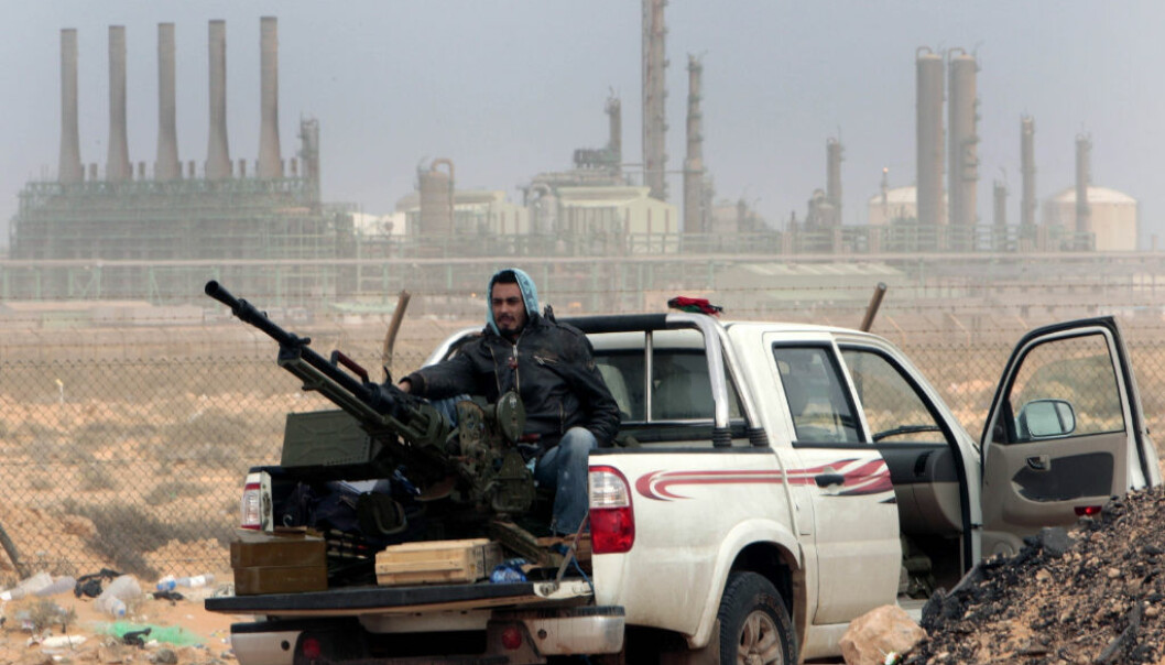 FILE - In this March 5, 2011 file photo, an anti-government rebel sits with an anti-aircraft weapon in front an oil refinery in Ras Lanouf, eastern Libya. The fight for Libya Äôs Ras Lanuf refinery and nearby Sidr depot threatens to spiral into open conflict between rival factions vying for power from east and west. With both sides claiming the facilities as their own but control unclear, decisive days lie ahead. (AP Photo/Hussein Malla, File)