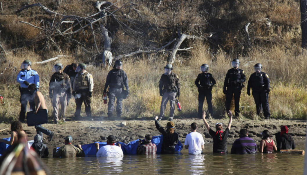 FILE - In this Nov. 2, 2016, file photo, protesters demonstrating against the expansion of the Dakota Access pipeline wade in cold creek waters confronting local police near Cannon Ball, N.D. North Dakota officials appear poised to go after the U.S. government  Äî and thus U.S. taxpayers  Äî to recoup more than $38 million in state expenses related to months of protests against the Dakota Access pipeline. (AP Photo/John L. Mone, File)