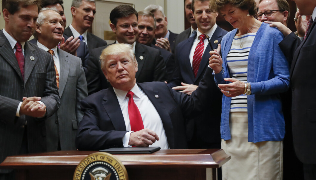 President Donald Trump, gives the pen he used to sign an Executive Order to Sen. Lisa Murkowski, R-Alaska, right, in the Roosevelt Room of the White House in Washington, Friday, April 28, 2017. The Executive Order directs the Interior Department to begin review of restrictive drilling policies for the outer-continental shelf. (AP Photo/Pablo Martinez Monsivais)