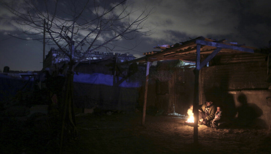 FILE -- In this Jan. 15, 2017 file photo, a Palestinian family warm themselves by a fire outside their makeshift house during a power cut in Khan Younis, southern Gaza Strip. GazaǃÙs 2 million people endure daily electricity cuts of 14 to 18 hours at a time and now face even longer blackouts because of an escalating power struggle between Palestinian governments. This comes as Muslims observe the holy month of Ramadan, when electricity consumption increases as the dawn-to-dusk fast is followed by elaborate meals and the devout stay up late into the night. (AP Photo/ Khalil Hamra, File)