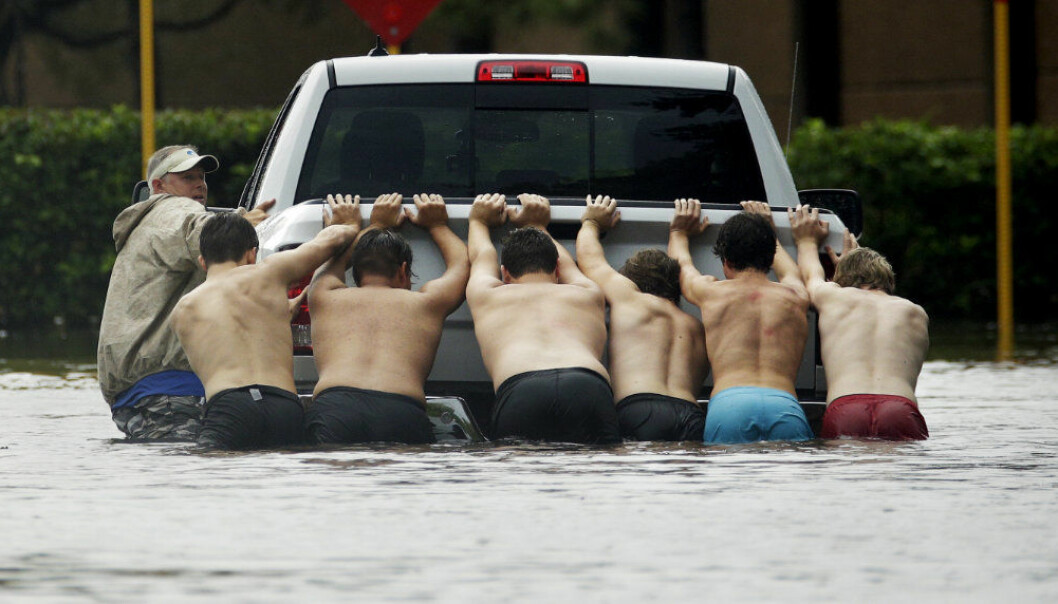 People push a stalled pickup to through a flooded street in Houston, after Tropical Storm Harvey dumped heavy rains Sunday, Aug. 27, 2017. The remnants of Hurricane Harvey sent devastating floods pouring into Houston Sunday as rising water chased thousands of people to rooftops or higher ground. (AP Photo/Charlie Riedel)
