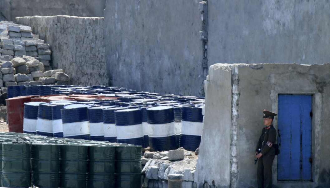 FILE - In this May 8, 2016, file photo, a North Korean solder stands guard near barrels stacked up near the river bank of the North Korean town of Sinuiju, opposite the Chinese border city of Dandong. China announced Saturday, Sept. 23, 2017 it will limit oil supplies to North Korea under U.N. sanctions starting Oct. 1, 2017, stepping up pressure on Pyongyang over its pursuit of nuclear and missile technology. (Chinatopix via AP, File)