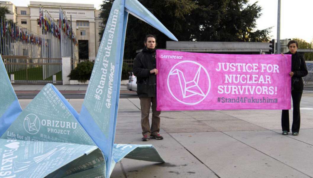 Two persons hold a banner next to a giant origami during a protest organized by Greenpeace  in front of the European headquarters of the United Nations, in Geneva, Switzerland, on Thursday, Oct. 12, 2017. This is an operation to support the work of mothers of families in the Fukushima region. (Martial Trezzini/Keystone via AP)