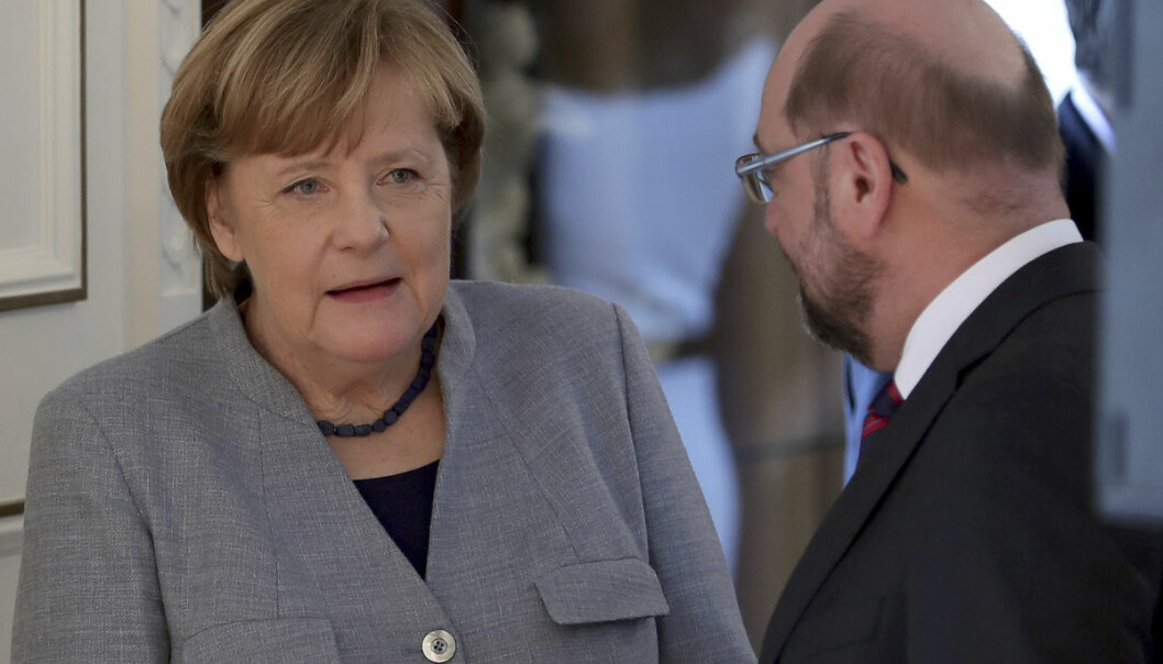 Martin Schulz, Chairman of the German Social Democratic Party (SPD), right, and German Chancellor Angela Merkel, left, talk as they queue up during a New Year's reception of German President Frank-Walter Steinmeier at the Bellevue palace in Berlin, Germany, Tuesday, Jan. 9, 2018. (AP Photo/Michael Sohn)