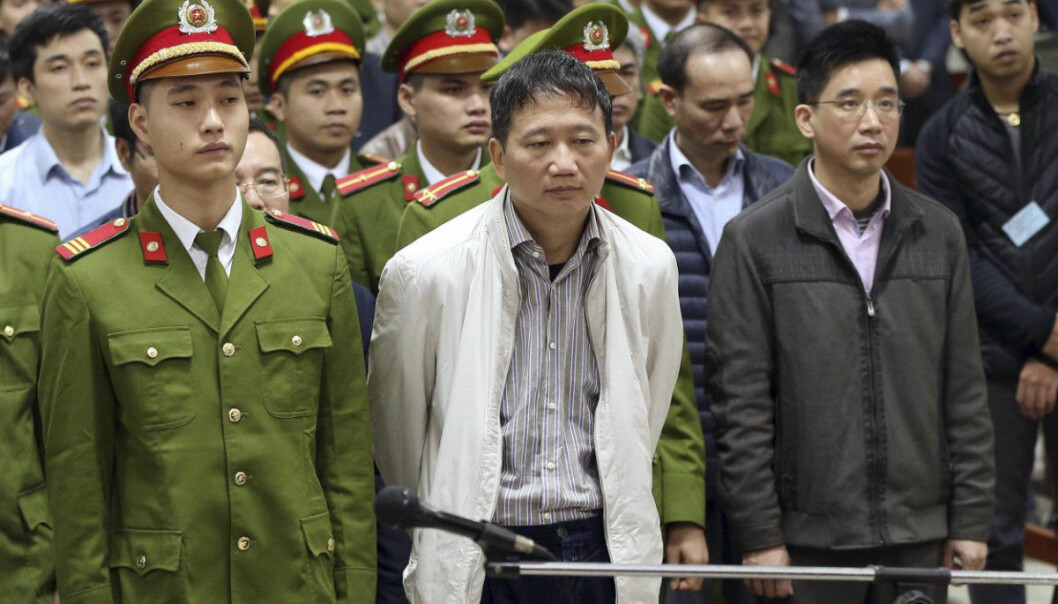 Trinh Xuan Thanh, center, listens to the verdict in Hanoi, Vietnam, Monday, Jan. 22, 2018. The former oil executive was sentenced to life in prison on charges of embezzlement and mismanagement at the end of the two-weeks trial that also involves 21 others including former Politburo Dinh La Thang. Germany accused Vietnam of kidnapping Thanh from a Berlin park in July, the charge Vietnam denied saying Thanh turned himself in to police voluntarily. (Doan Tan/ Vietnam News Agency via AP)