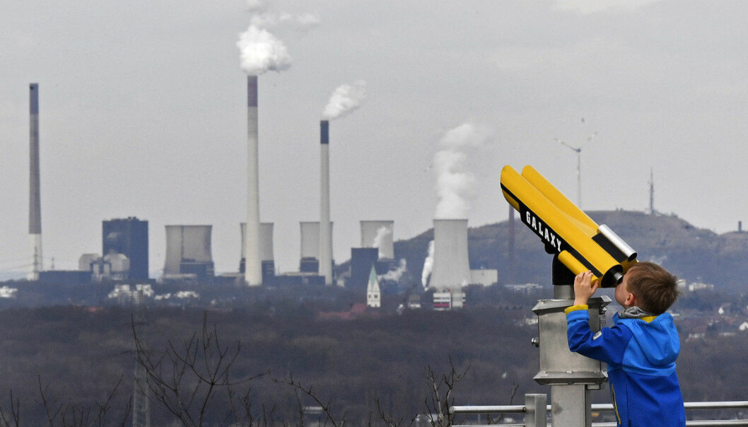 A boy watches the Gelsenkirchen coal-fired power plant through a telescope from a mine pile in Bottrop, Germany, Friday, March 9, 2018. Germany pushes on a fossil fuel phase out to fight against climate change. (AP Photo/Martin Meissner)