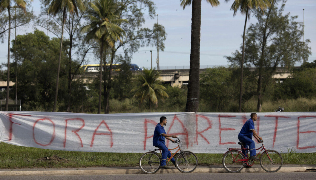 """Workers pedal their bicycles past a banner with a message that reads in Portuguese: """"Get out Parente"""", in reference to  Pedro Parente, the president of the state-owned oil company, at the entrance of a Petrobras refinery during a strike in Duque da Caxias, Brazil, Wednesday, May 30, 2018. Brazilian oil workers began a 3-day strike to demand a drop in the price of cooking gas. (AP Photo/Leo Correa)"""