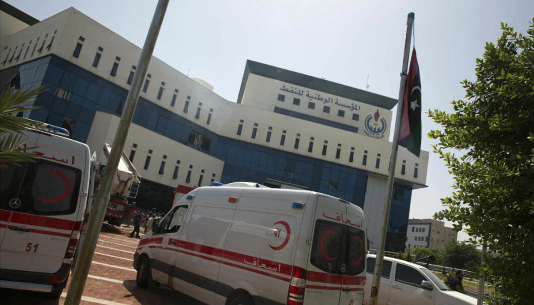 Ambulances and firefighters gather at the headquarters of the national oil company after an attack by gunmen in Tripoli, Libya, Monday, Sept. 10, 2018. Officials say security forces of Libya's U.N.-backed government stormed the building in the capital Tripoli after gunmen had earlier gone in, taking hostages and starting a fire. They say at least one explosion rocked the building soon after the gunmen stormed it, starting the blaze that swiftly spread through the lower floors. (AP Photo/Mohamed Ben Khalifa)