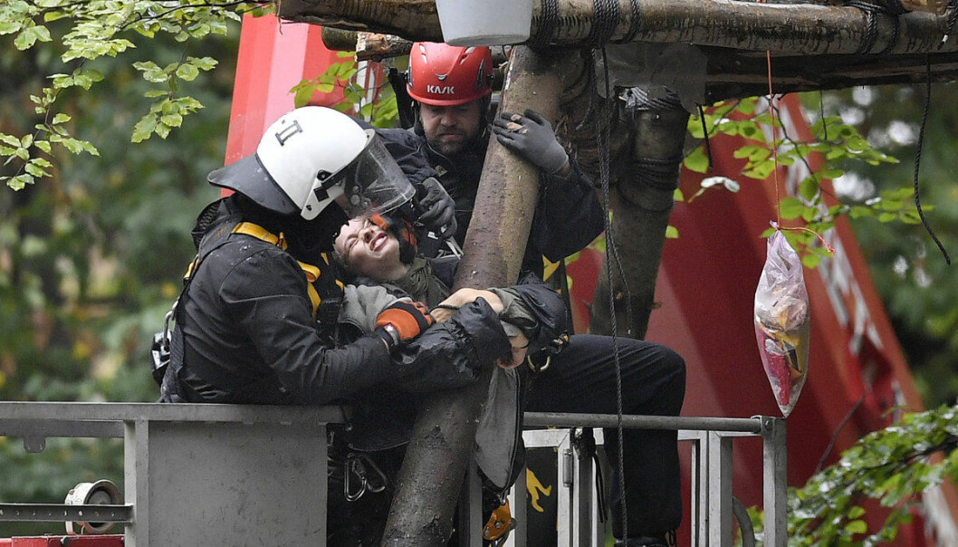 FILE - In this Sept. 13, 2018 file photo rolice removes activists from treehouses in the forest 'Hambacher Forst' in Kerpen, western Germany. On Friday, Oct. 5, 2018 a German court has ordered a temporary halt to plans to fell part of a forest in the west of the country to allow the expansion of a coal mine. (AP Photo/Martin Meissner, file)