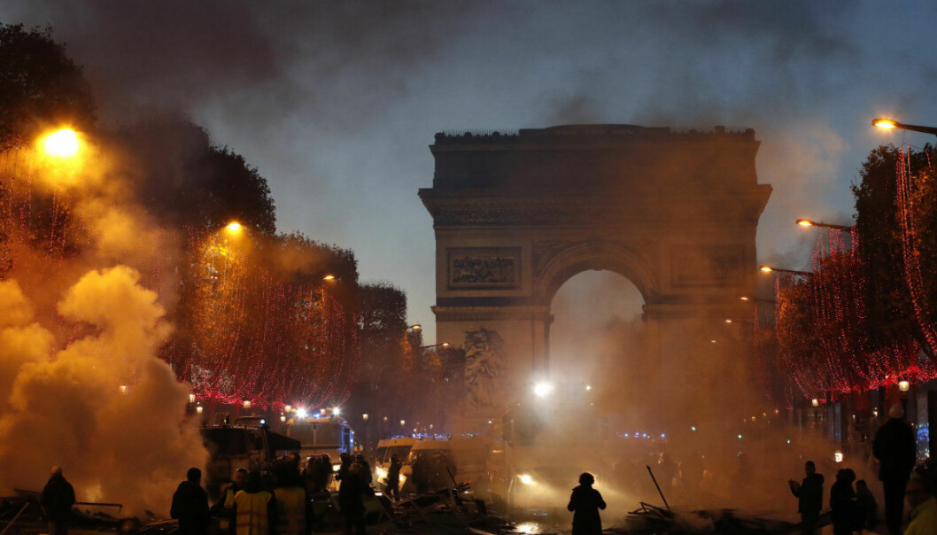 Plumes of smoke are seen near the Arc de Triomphe on the Champs-Elysees avenue decorated with the Christmas lightings during a protest against tax Saturday, Nov. 24, 2018 in Paris. French police fired tear gas and water cannons to disperse violent demonstrators in Paris, as thousands gathered in the capital and beyond and staged road blockades to vent anger against rising fuel taxes. (AP Photo/Christophe Ena)