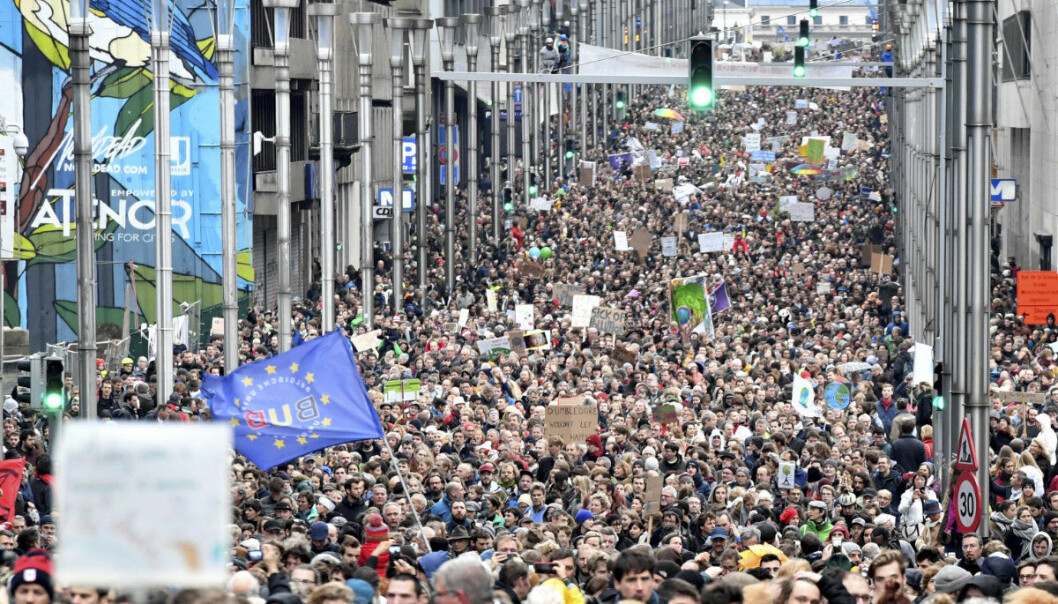 Demonstrators hold signs and wave flags as they march in the main EU quarter during a 'Claim the Climate' march in Brussels, Sunday, Dec. 2, 2018. The climate change conference, COP24, will take place in Poland from Dec. 2-14. (AP Photo/Geert Vanden Wijngaert)