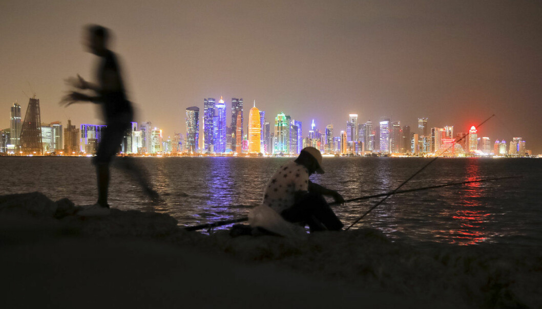 In this Nov. 2, 2018 picture men fish, backdropped by the city skyline Doha, Qatar. Eight stadiums scattered in a 30-mile radius that will host 32 teams from across the planet are in various stages of development, most of them trying to walk the treacherous line of paying homage to the region's history while simultaneously avoiding becoming an expensive and unused relic once the party ends and everyone else goes home. (AP Photo/Vadim Ghirda)
