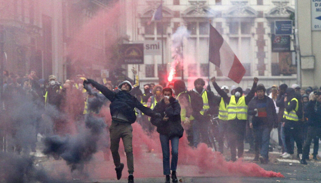 Demonstrators clashes with police in Paris, France, Saturday, Dec. 8, 2018. Crowds of protesters angry at President Emmanuel Macron and France's high taxes tried to converge on the presidential palace Saturday, some scuffling with police firing tear gas, amid exceptional security measures aimed at preventing a repeat of last week's rioting. (AP Photo/Thibault Camus)