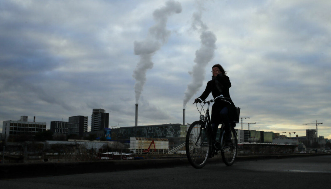 Smoke rise from a factory as a woman rides her bicycle in Paris, France, Tuesday, Dec. 4, 2018. The COP24 summit on climate change is taking place in Poland's southern city of Katowice from December 2 to 14, 2018. (AP Photo/Francois Mori)