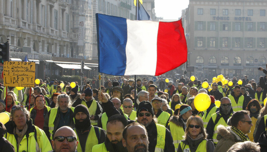 Demonstrators wearing their yellow vests brandish a French flag during a demonstration in Marseille, southern France, Saturday, Dec. 29, 2018.  The yellow vest movement held several peaceful demonstrations in cities and towns around France, including about 1,500 people who marched through Marseille. (AP Photo/Claude Paris)