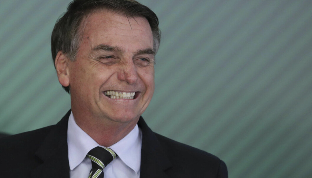Brazil's President Jair Bolsonaro smiles during a ceremony where he signed a decree loosening restrictions on owning a firearm at Planalto presidential palace in Brasilia, Brazil, Tuesday, Jan. 15, 2019. Before, non-military or police who wanted to own a gun had to justify their interest as part of the process, and now wide categories of people will qualify, like those in rural areas, or urban areas with high levels of homicide, business owners, gun collectors and hunters. (AP Photo/Eraldo Peres)