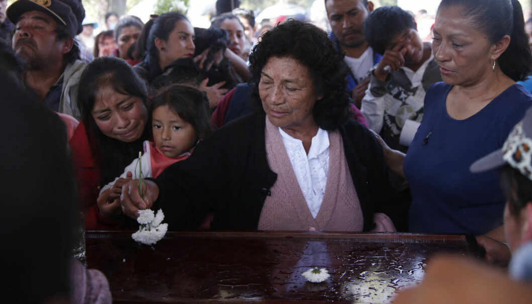 A woman sprinkles holy water, using a flower, on the coffin of a person who died when a gas pipeline exploded in the village of Tlahuelilpan, Mexico, Sunday Jan. 20, 2019. A massive fireball that engulfed locals scooping up fuel spilling from a pipeline ruptured by thieves in central Mexico killed dozens of people and badly burned dozens more on Jan. 18. (AP Photo/Claudio Cruz)