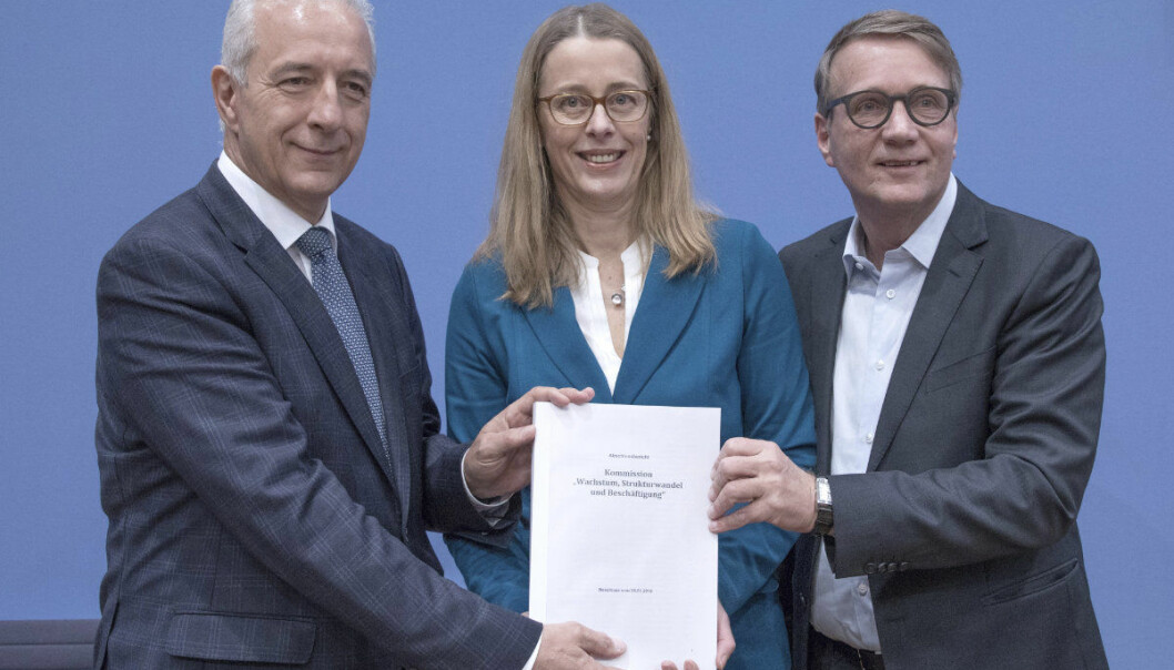 Heads of Germany's coal commission Stanislaw Tillich, left, Barbara Praetorius, center, and Ronald Pofalla show a paper with the results of a meeting in Berlin, Germany, Saturday, Jan.26,2019. ( Joerg Carstensen/dpa via AP)