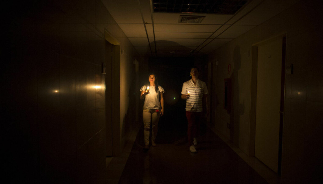 Relatives of a patient walk in the darkened hall of a clinic with a candle lighting the way, during a power outage in Caracas, Venezuela, Thursday, March 7, 2019. A power outage left much of Venezuela in the dark early Thursday evening in what appeared to be one of the largest blackouts yet in a country where power failures have become increasingly common. (AP Photo/Ariana Cubillos)