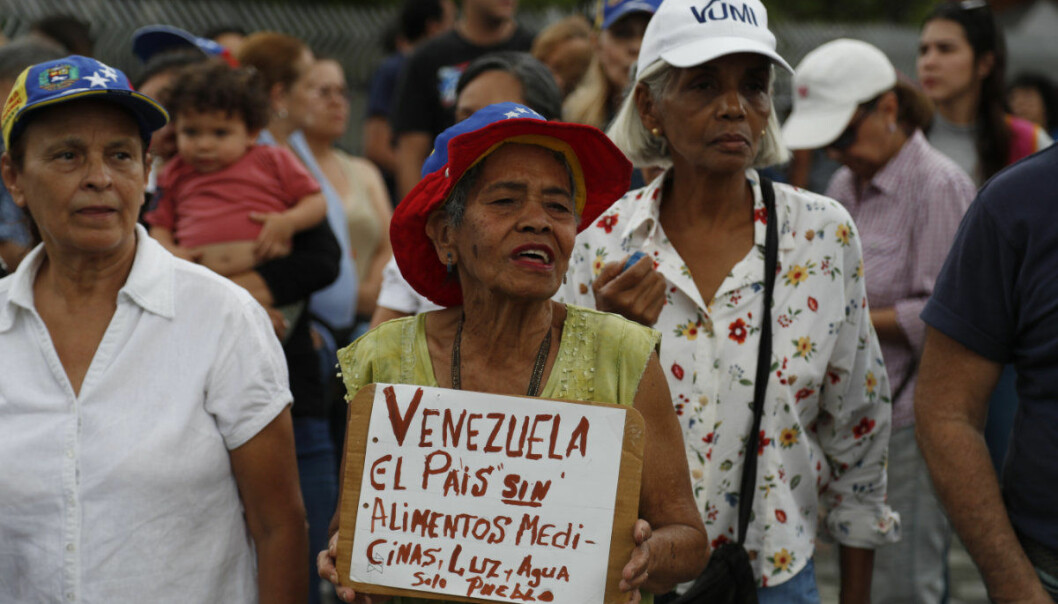 """A woman holds a sign that reads in Spanish: """"Venezuela, a country without food, medicine, light, and water. Only people."""" during a protest against the government of Venezuela's President Nicolas Maduro in Caracas, Venezuela, Tuesday, March 12, 2019. Most people have been deprived of power, water and communications since last Thursday when nationwide power outages first hit, abruptly worsening conditions in a nation already struggling with hyperinflation and shortages of food and medicine. (AP Photo/Eduardo Verdugo)"""